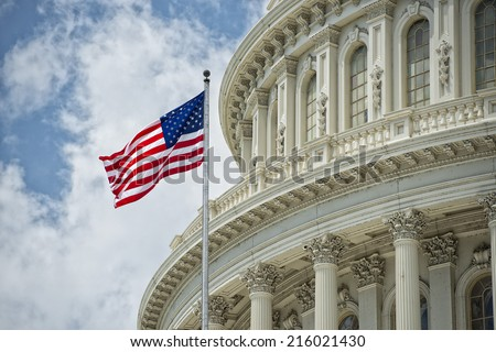 Washington DC Capitol dome detail with waving american flag Royalty-Free Stock Photo #216021430
