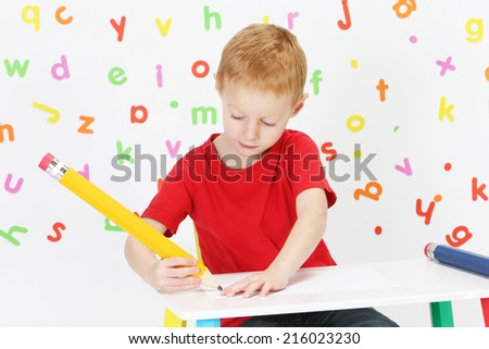 Little boy writing with a big pen #216023230
