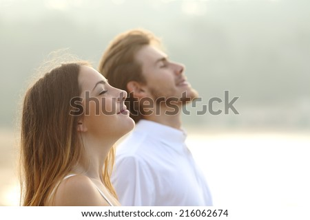Profile of a couple of man and woman breathing deep fresh air together at sunset                Royalty-Free Stock Photo #216062674