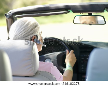 Woman with hands-free device in car, rear view #216103378