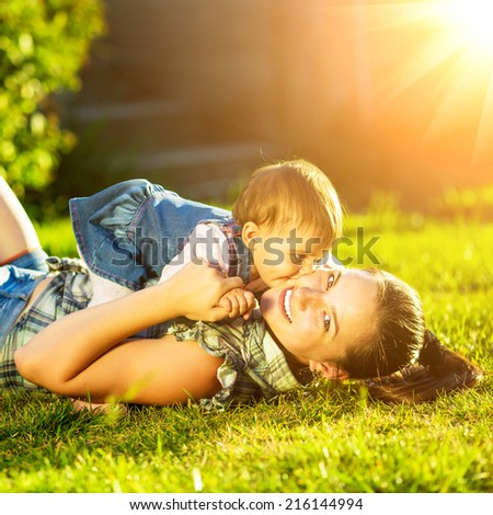 Mother and baby daughter are playing outdoors. Young mom and her cute little baby-girl are having fun in the sunny garden. Happy childhood and parenthood concept.  #216144994
