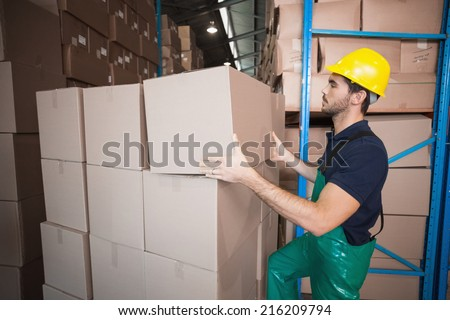 Warehouse worker loading up a pallet in a large warehouse #216209794
