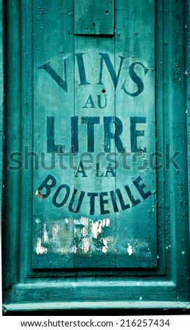 """Old wine and spirit cellar sign. Text in French """"Vins au litre, a la bouteille"""" meaning """"Wine selling by liters or in bottles"""". Toned photo."""
