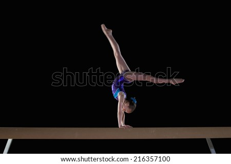 Young female gymnast performing handstand on balance beam, side view