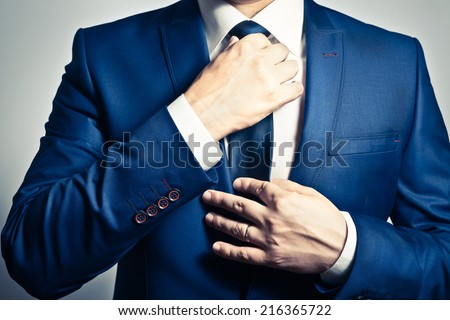 Businessman in blue suit tying the necktie Royalty-Free Stock Photo #216365722