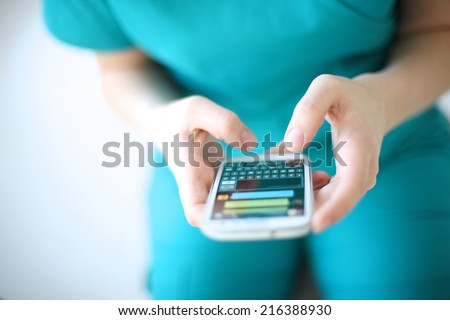 Hands of young woman sending text message from smart phone at work Royalty-Free Stock Photo #216388930