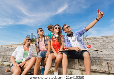friendship, leisure, summer, technology and people concept - group of smiling friends with skateboard and smartphone making selfie outdoors #216410350