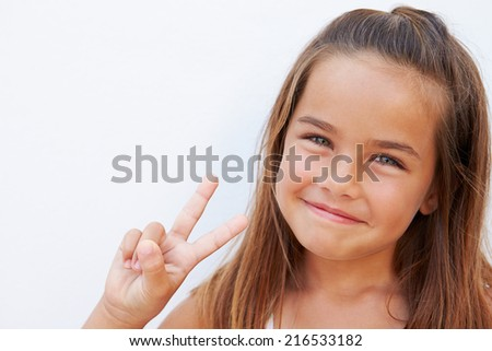 Pretty Hispanic Girl Standing By Wall Making Peace Sign