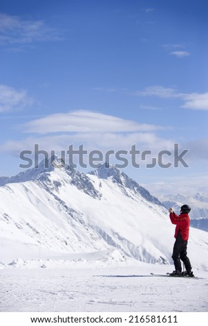 Skier taking photograph with digital camera on snowy mountain #216581611