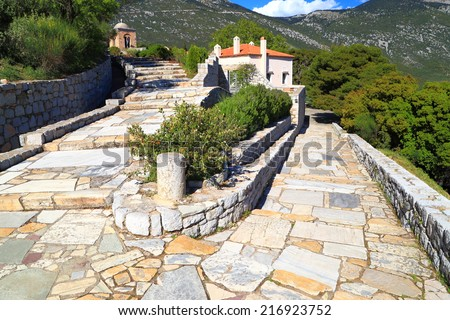 Sunny road paved with stones leading to a Byzantine monastery, Greece #216923752