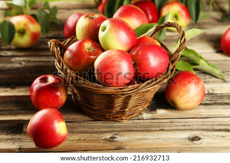 Apples in basket on brown wooden background #216932713