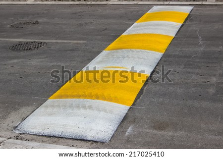 Freshly painted speed bump for slowing traffic near school. Selective focus. #217025410