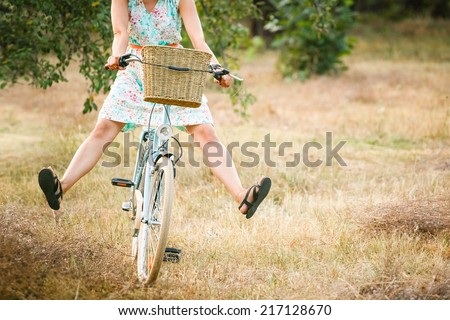 Woman riding bicycle with her legs in the air. Summer fun  #217128670
