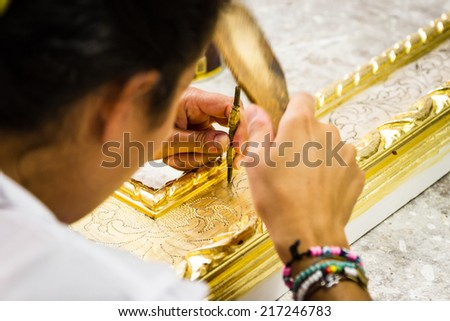 Woman working on a picture frame in her workshop