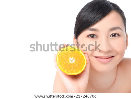 Portrait of an attractive young girl holding a slice of orange #217248706