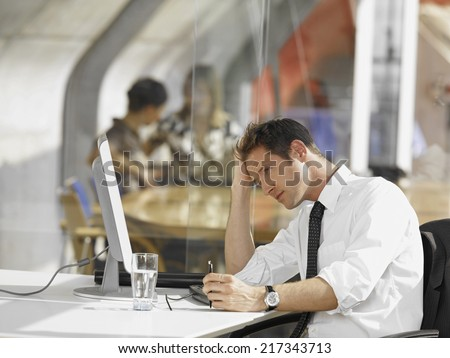 Businessman sitting in front of a desktop PC #217343713