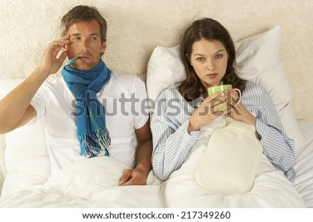 Portrait of a mid adult woman reclining with a mid adult man on the bed and drinking a cup of tea #217349260