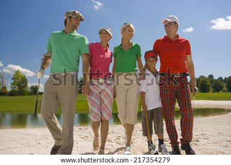 Two mid adult couples with a boy walking on the sand trap on a golf course #217354279