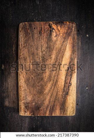 Old dark cutting board on brown wooden table, background #217387390