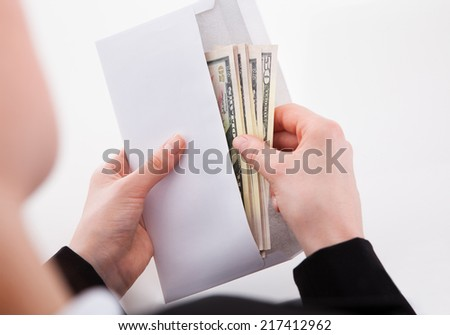 Cropped image of businesswoman putting American banknotes in envelope at office #217412962