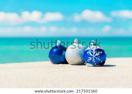 Christmas tree decorations on sea beach sand - winter holidays in hot countries concept #217501360
