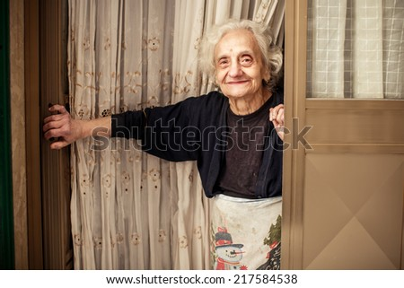 BARI, ITALY - NOVEMBER 2, 2013: Old woman looking out of the door in Bari on November 2, 2013, Italy #217584538