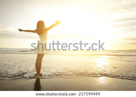 Smile Freedom and happiness woman on beach. She is enjoying serene ocean nature during travel holidays vacation outdoors. asian beauty #217599499