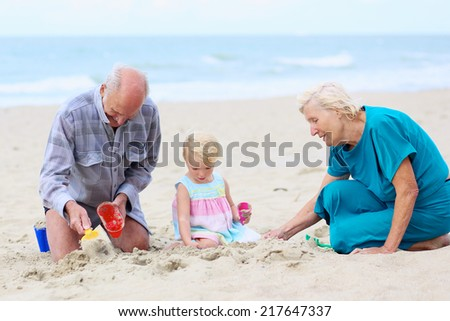 Happy grandparents playing with their granddaughter, cute toddler girl, at the beach building sand castles with plastic toys - active retirement concept #217647337