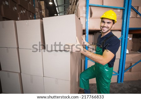 Warehouse worker loading up a pallet in a large warehouse #217766833