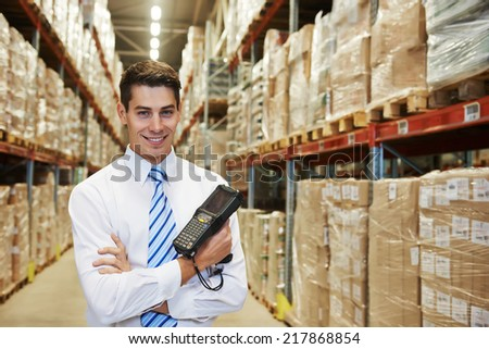 smiling manager in warehouse with bar code scanner #217868854