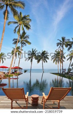 KOH SAMUI, THAILAND - APRIL 4, 2011: Great review for a luxury beachfront pool and the ocean. Two convenient comfortable guest sun loungers and a bedside table are worth on a wooden platform #218019739