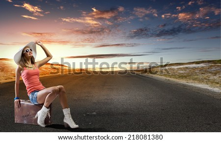 Young pretty girl traveler sitting on suitcase aside of road #218081380