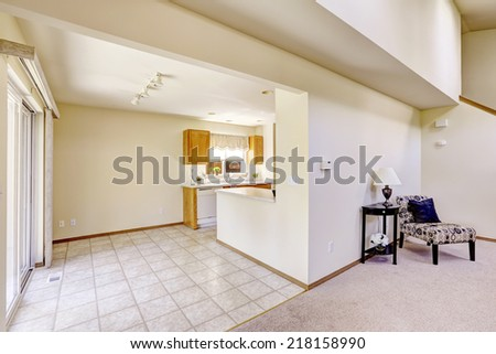 Bright rooms in empty house. Kitchen area with tile floor and corner furnished with chair and table #218158990