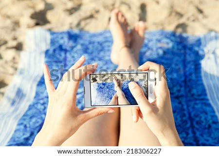 Close up of a young and attractive woman tourist hands together holding a modern technology smartphone and taking a selfie picture of her own legs while laying down on a sandy beach on holiday.