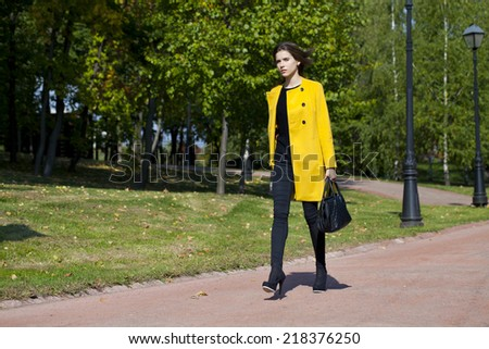 Beautiful young woman in yellow coat in autumn street #218376250