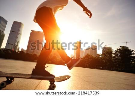 woman skateboarder skateboarding at  sunrise city  #218417539