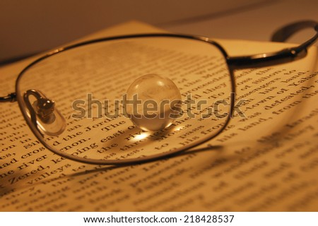 Glass Marble through Glasses Lens on Book - Metaphor for Inspiration, Insight #218428537
