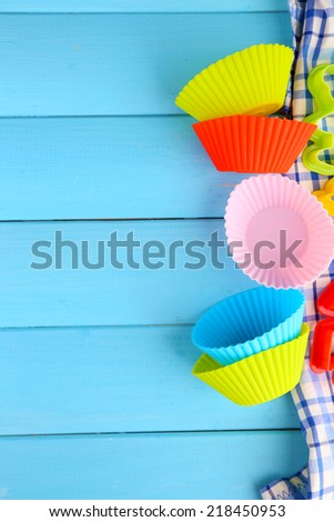 Plastic bowls and molds for cutting on color wooden background #218450953