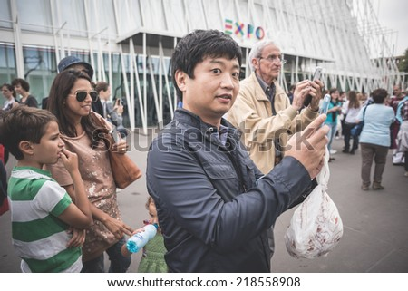 MILAN, ITALY - SEPTEMBER 20: People during Milan Fashion week in Milan, Italy on September, 20 2014. Eccentric and fashionable people in the city during fashion week wait for models and famous people #218558908