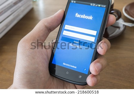 THAILAND - SEPTEMBER 05, 2014: Facebook application login screen on htc mobile with hand holding. #218600518
