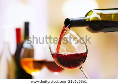 Red wine pouring into wine glass, close-up Royalty-Free Stock Photo #218626861