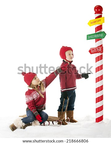 Two young children are on their way to the North Pole.  The sister points the way on one of Santa's directional signs.  On a white background with plenty of space for your text.