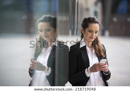 Portrait of a Caucasian businesswoman standing outside using mobile phone to send a message. #218719048