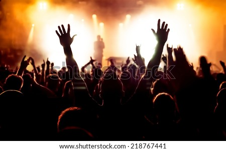 silhouettes of concert crowd in front of bright stage lights Royalty-Free Stock Photo #218767441