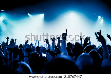 silhouettes of concert crowd in front of bright stage lights #218767447
