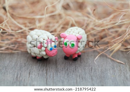 Plasticine world - little homemade white sheep with blue and green eyes stand on a farm on background of hay, selective focus and place for text