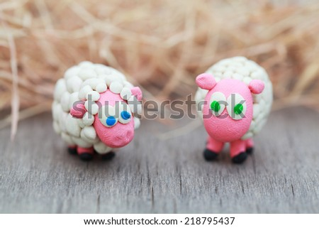 Plasticine world - little homemade white sheep with blue and green eyes stand on a farm on background of hay, selective focus