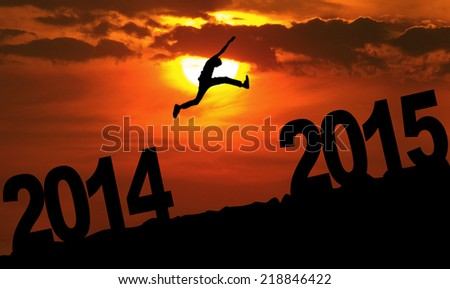 Silhouette person jumping over 2015 on the hill at sunset Royalty-Free Stock Photo #218846422