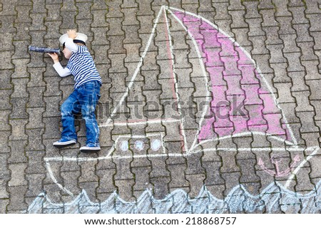 Creative leisure for children: Funny little boy of four years having fun with ship or boat picture drawing with chalk.