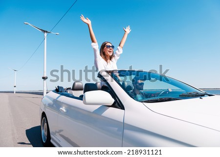 Couple in cabriolet. Happy young couple enjoying road trip in their convertible while woman raising arms and smiling  #218931121